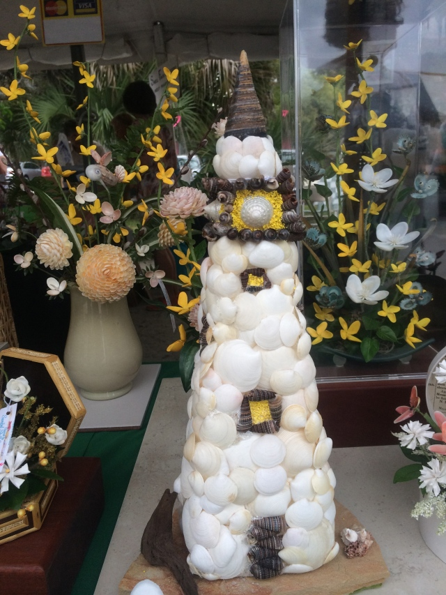 This lighthouse is created with a variety of shells.  Note that the flower petals in the background are also made entirely of shells.
