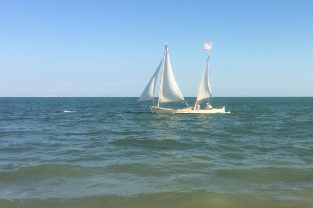 Interesting open boat sails close to the island shore.