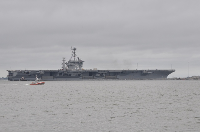 Security vessels make sure that others maintain a wide berth around Aircraft Carrier 75.