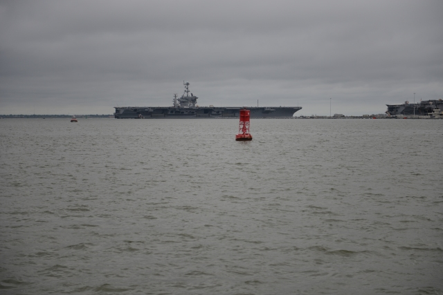 An aircraft carrier glides smoothly into port.