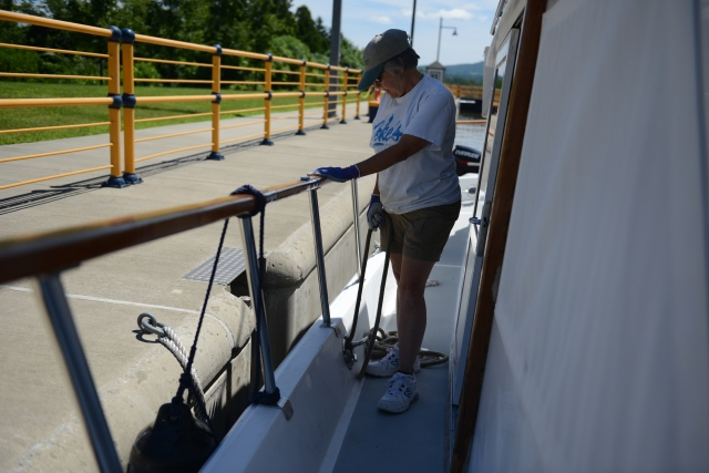 Ann tends the line that helps hold the Traveler steady in the lock.  The line must be continually adjusted as water enters the lock to lift the boat to the higher level.