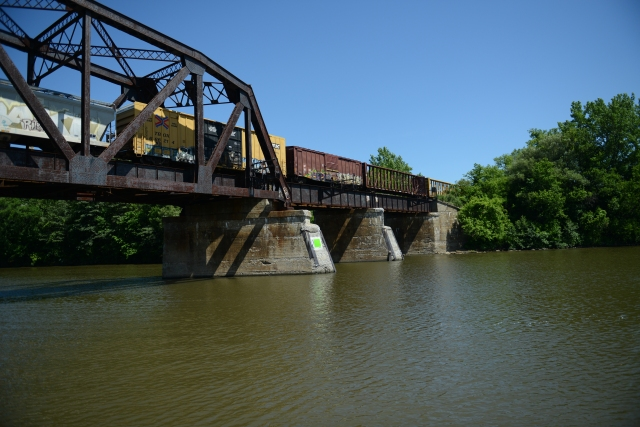 A train crosses over the bridge as we pass under it.