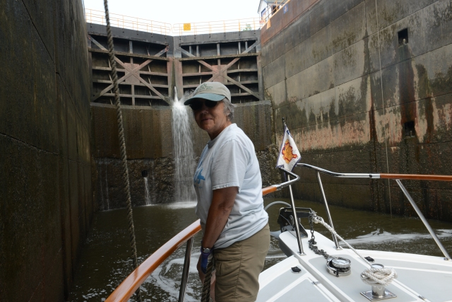 Ann holding the bow line to keep the Traveler safe during a lock passage.